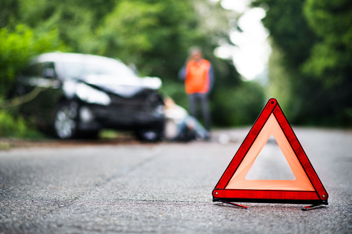 A close up of a red emergency triangle on the road in front of a car after an accident.